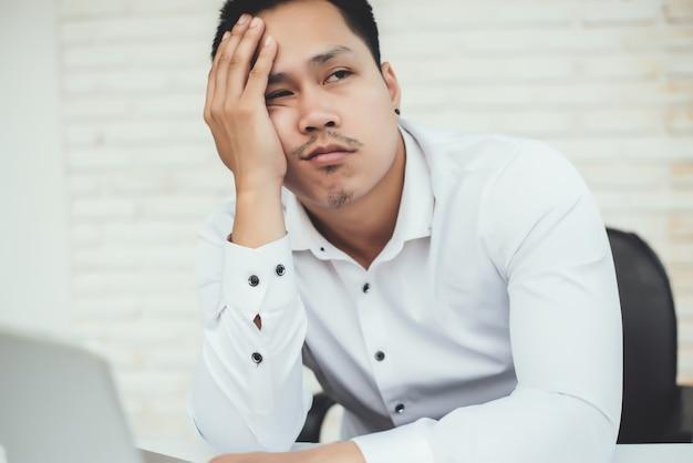 Homem de negócios jovem bonito com local de trabalho no escritório criativo