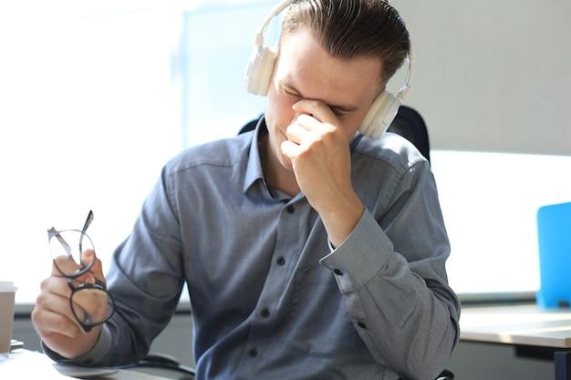 Homem de negócios jovem bonito com os olhos fechados, tocando o rosto com as mãos enquanto está sentado no local de trabalho no escritório.