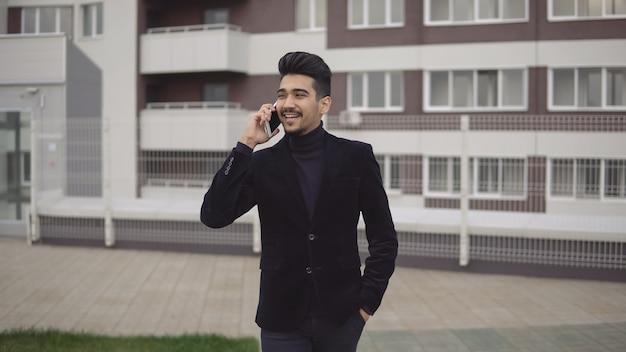 Homem de negócios jovem bonito falando no smartphone, sorrindo feliz vestindo paletó ao ar livre. profissional urbano masculino na casa dos 20 anos.