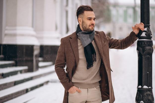 Homem de negócios jovem bonito lá fora no inverno