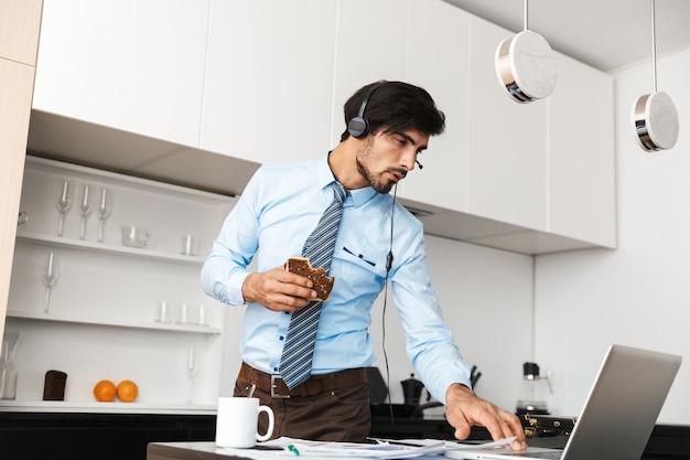 Homem de negócios jovem bonito na cozinha comer sanduíche usando o computador portátil com fones de ouvido.