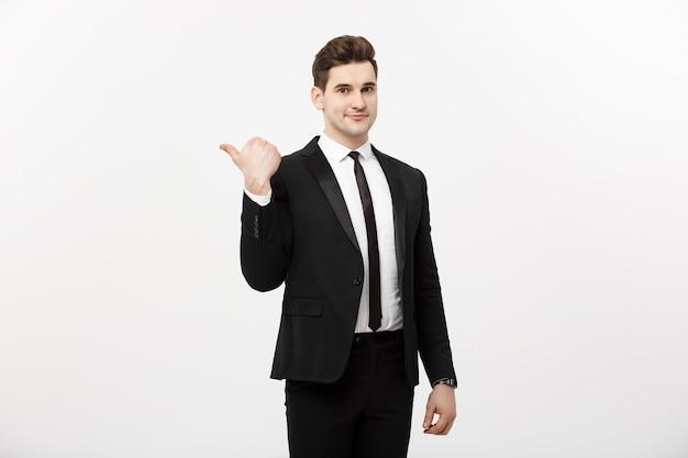 Homem de negócios jovem bonito sorriso feliz apontar o dedo para o espaço vazio da cópia, empresário mostrando o lado apontando, conceito de produto de propaganda, isolado sobre fundo branco.