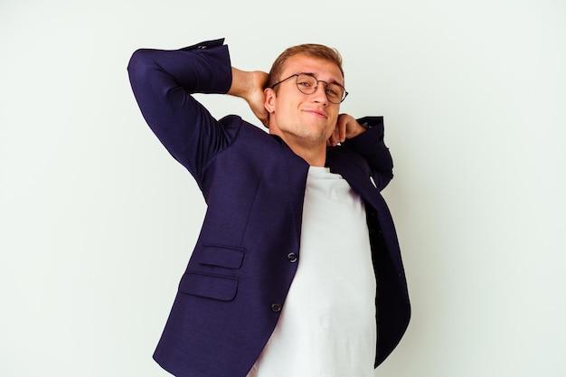 Homem de negócios jovem caucasiano isolado no branco, esticando os braços, posição relaxada.