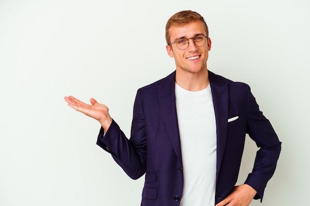 Homem de negócios jovem caucasiano isolado no fundo branco, mostrando um espaço de cópia na palma da mão e segurando a outra mão na cintura.
