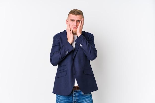 Homem de negócios jovem caucasiano lamentando e chorando desconsoladamente.