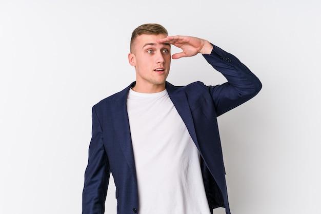 Homem de negócios jovem caucasiano olhando longe mantendo a mão na testa.