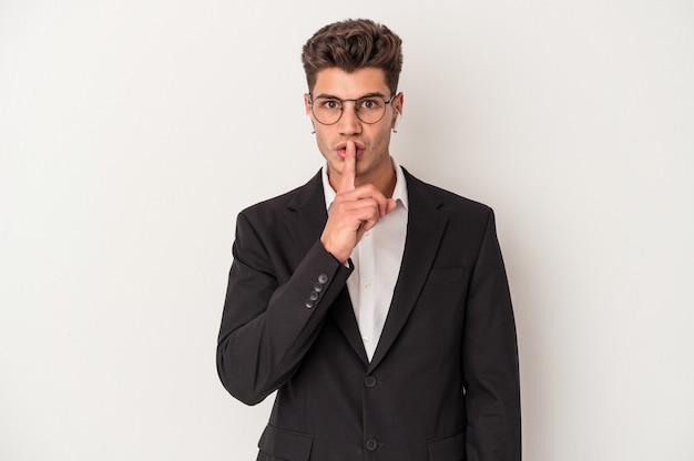 Homem de negócios jovem caucasiano usando fones de ouvido isolados no fundo branco, mantendo um segredo ou pedindo silêncio.