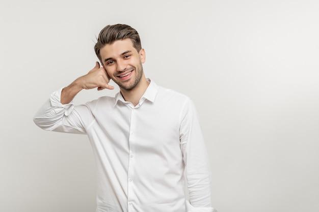 Homem de negócios jovem com a barba por fazer sorridente fazendo gesto de celular isolado sobre fundo branco