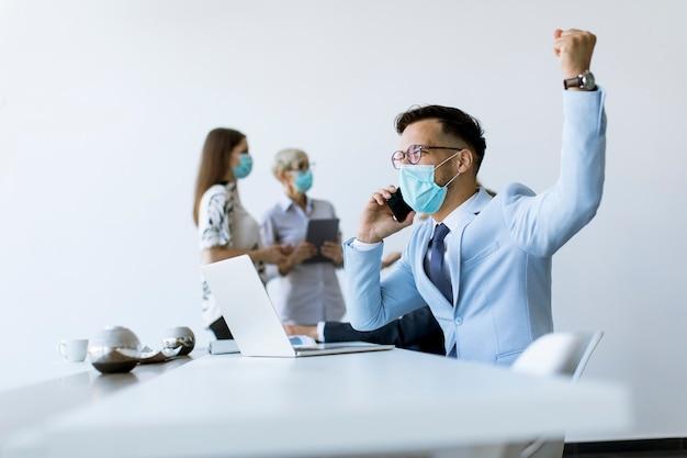 Homem de negócios jovem com máscara protetora médica trabalha em um laptop e usando telefone celular