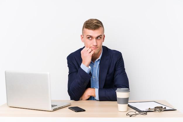 Homem de negócios jovem com um laptop confuso, sente-se duvidoso e inseguro.