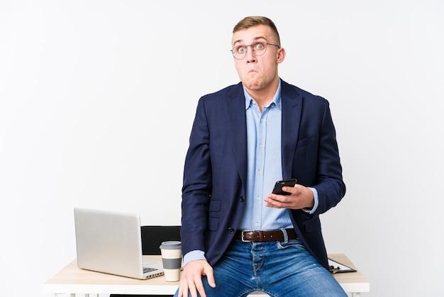 Homem de negócios jovem com um laptop encolhe os ombros e abre os olhos confusos.