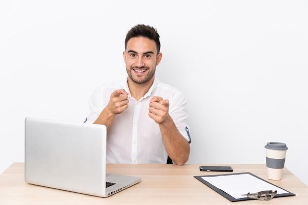 Homem de negócios jovem com um telefone móvel em um local de trabalho aponta o dedo para você