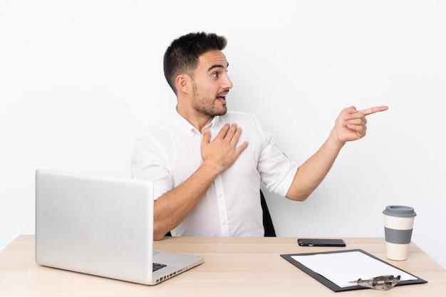 Homem de negócios jovem com um telefone móvel em um local de trabalho, apontando o dedo para o lado