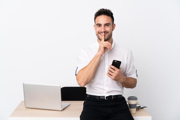 Homem de negócios jovem com um telefone móvel em um local de trabalho fazendo o gesto de silêncio