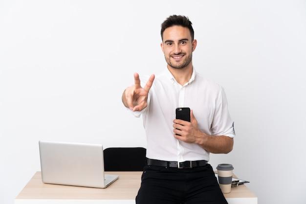 Homem de negócios jovem com um telefone móvel em um local de trabalho, sorrindo e mostrando sinal de vitória
