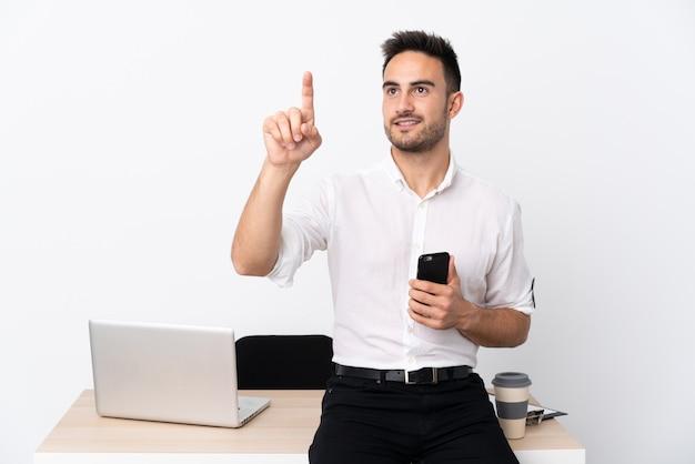 Homem de negócios jovem com um telefone móvel em um local de trabalho tocando na tela transparente