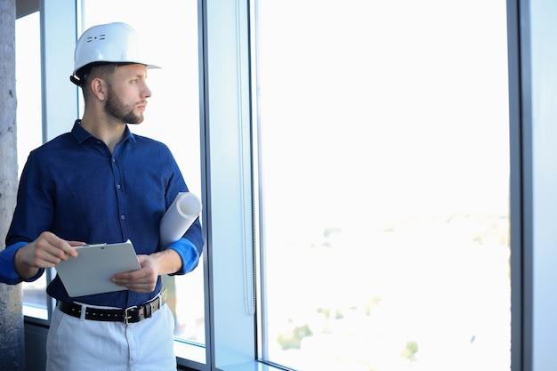 Homem de negócios jovem confiante na camisa, examinando a planta em pé contra uma janela no escritório.
