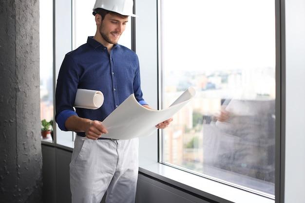 Homem de negócios jovem confiante no capacete de segurança segurando a planta e desviar o olhar em pé dentro de casa.