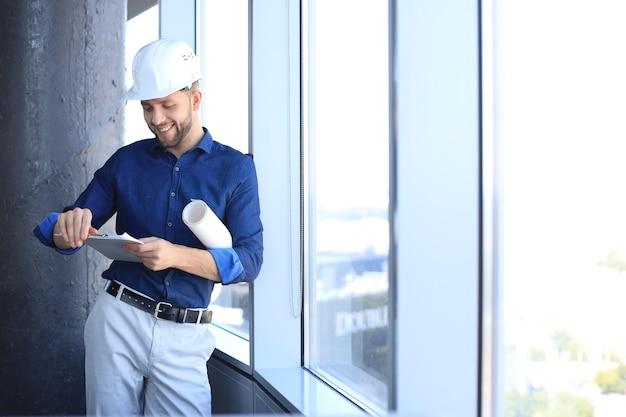 Homem de negócios jovem confiante no capacete de segurança segurando a planta e olhando para documentos em pé dentro de casa.