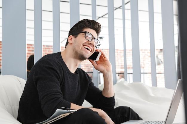 Homem de negócios jovem confiante trabalhando no escritório enquanto está sentado em um sofá, falando no celular