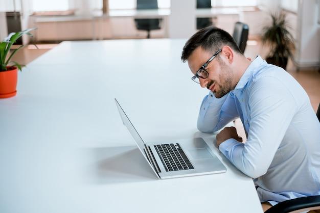 Homem de negócios jovem confuso trabalhando no computador portátil no interior do escritório moderno arranque.