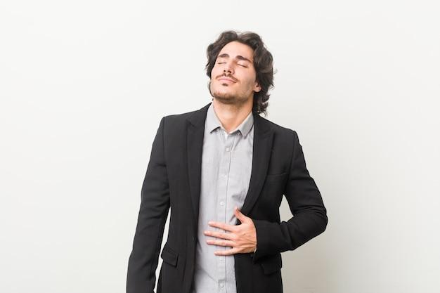 Homem de negócios jovem contra um fundo branco toca a barriga, sorri suavemente
