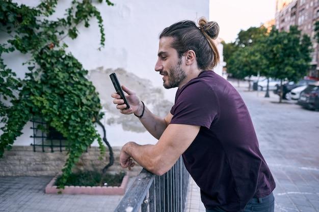 Homem de negócios jovem de cabelos compridos usando seu telefone na rua