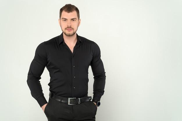Homem de negócios jovem de constituição atlética, de terno e camisa preta, colocando as mãos nos bolsos em um fundo branco isolado
