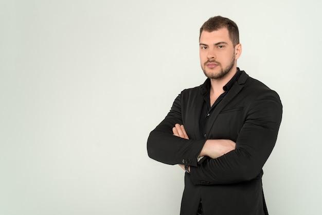 Homem de negócios jovem de constituição atlética, de terno e camisa preta, com os braços cruzados em um fundo branco isolado Foto Premium