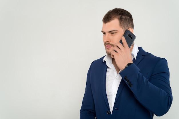 Homem de negócios jovem de constituição atlética, de terno e camisa preta, falando ao telefone celular em um fundo branco isolado