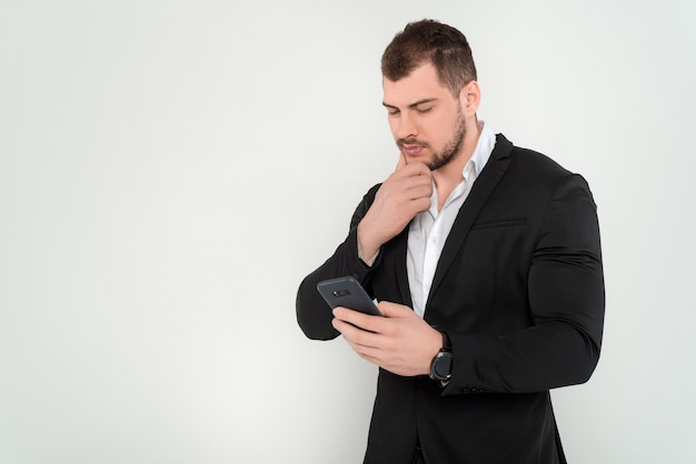 Homem de negócios jovem de constituição atlética, de terno e camisa preta lendo algo no celular em um fundo branco isolado
