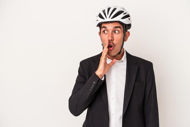 Homem de negócios jovem de raça mista com capacete de bicicleta isolado no fundo branco está contando notícias secretas sobre a frenagem e olhando para o lado