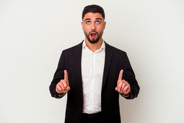 Homem de negócios jovem de raça mista isolado no fundo branco, apontando para cima com a boca aberta.