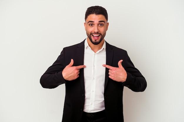 Homem de negócios jovem de raça mista isolado no fundo branco surpreso apontando com o dedo, sorrindo amplamente.