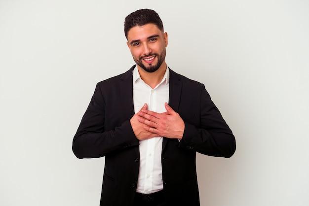 Homem de negócios jovem de raça mista, isolado no fundo branco, tem uma expressão amigável, pressionando a palma da mão no peito.