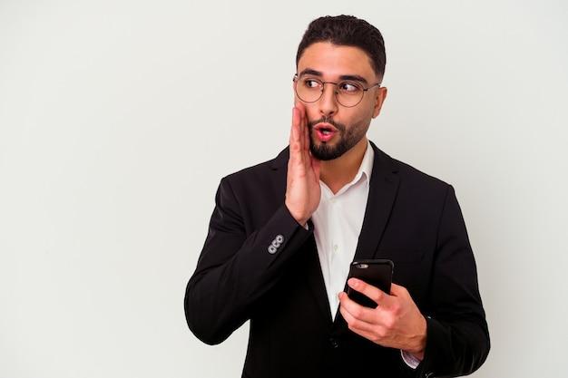 Homem de negócios jovem de raça mista segurando um homem de telefone celular isolado no fundo branco dizendo uma notícia secreta de travagem e olhando para o lado