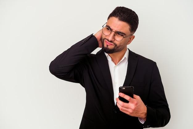 Homem de negócios jovem de raça mista segurando um homem de telefone celular isolado no fundo branco, tocando a parte de trás da cabeça, pensando e fazendo uma escolha.
