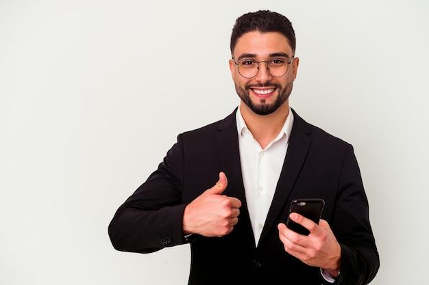 Homem de negócios jovem de raça mista segurando um telefone celular isolado no branco, sorrindo e levantando o polegar