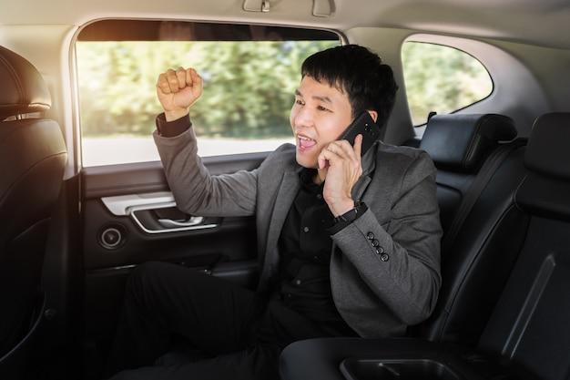 Homem de negócios jovem de sucesso falando em um telefone celular enquanto está sentado no banco de trás do carro