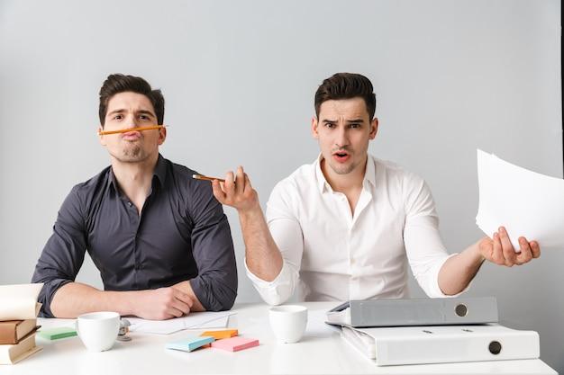 Homem de negócios jovem descontente olhando a câmera enquanto seu colega se divertindo