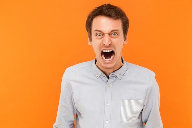 Homem de negócios jovem e adulto a gritar com a raiva da câmera e o conceito maluco