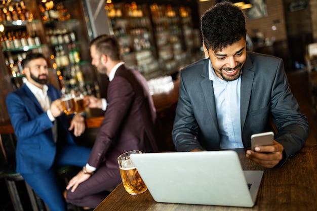 Homem de negócios jovem e bonito, blogueiro ou remoto trabalhando com laptop em restaurante