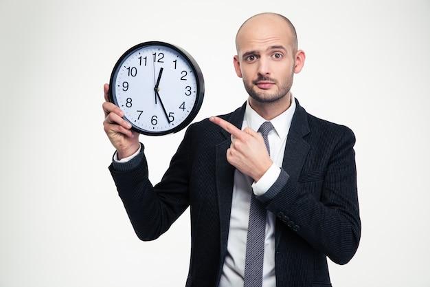 Homem de negócios jovem e bonito de terno preto e gravata apontando no relógio sobre a parede branca