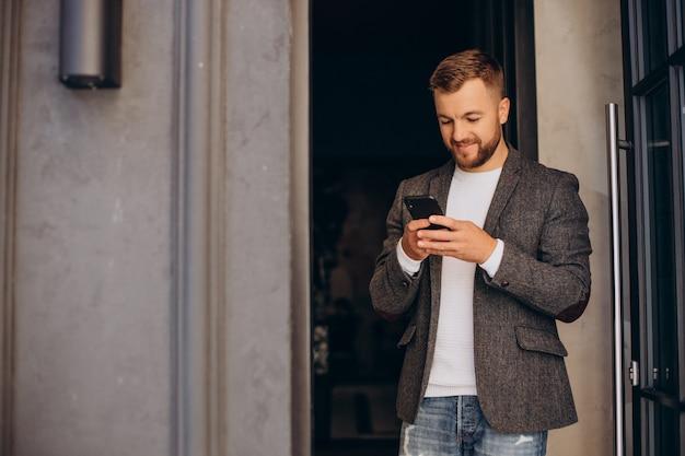 Homem de negócios jovem e bonito usando o telefone na rua