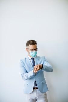 Homem de negócios jovem e elegante com máscara facial fica junto à parede no escritório e verificando o tempo
