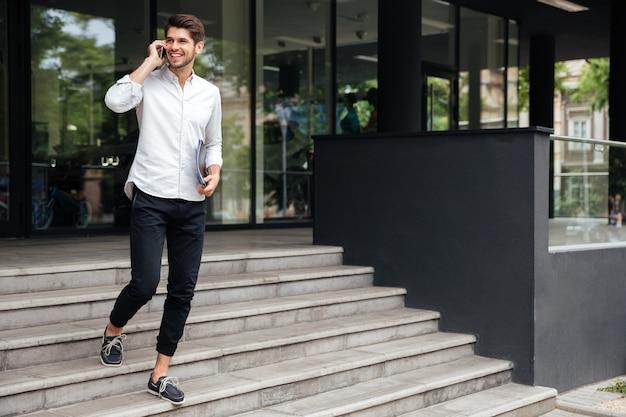Homem de negócios jovem e feliz com pastas andando e falando no celular ao ar livre