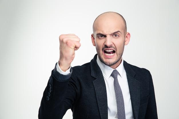 Homem de negócios jovem e furioso em trajes formais gritando e mostrando o punho fechado sobre uma parede branca