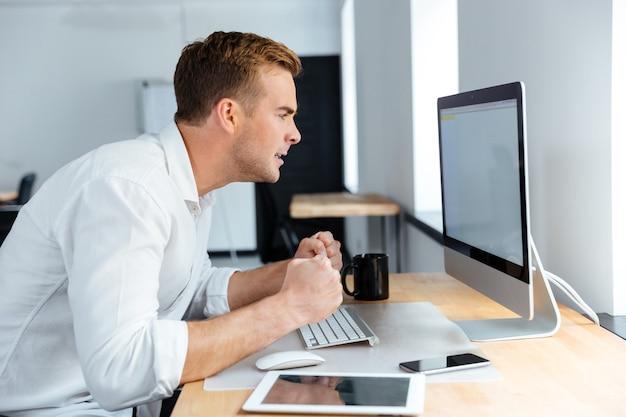 Homem de negócios jovem e irritado sentado e trabalhando com um computador de tela em branco no escritório