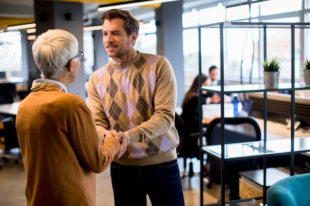 Homem de negócios jovem e mulher de negócios sênior, apertando as mãos no escritório