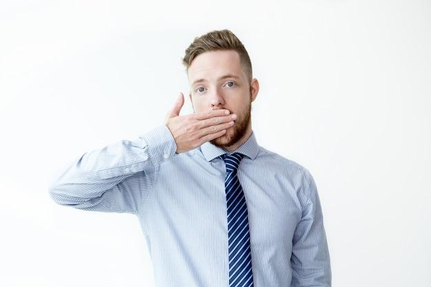 Homem de negócios jovem e serio que cobre a boca
